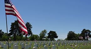 A big American flag at half staff and small American flags wave in the wind beside the tombstones at
